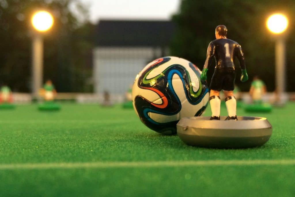 Subbuteo goalie with ball on pitch